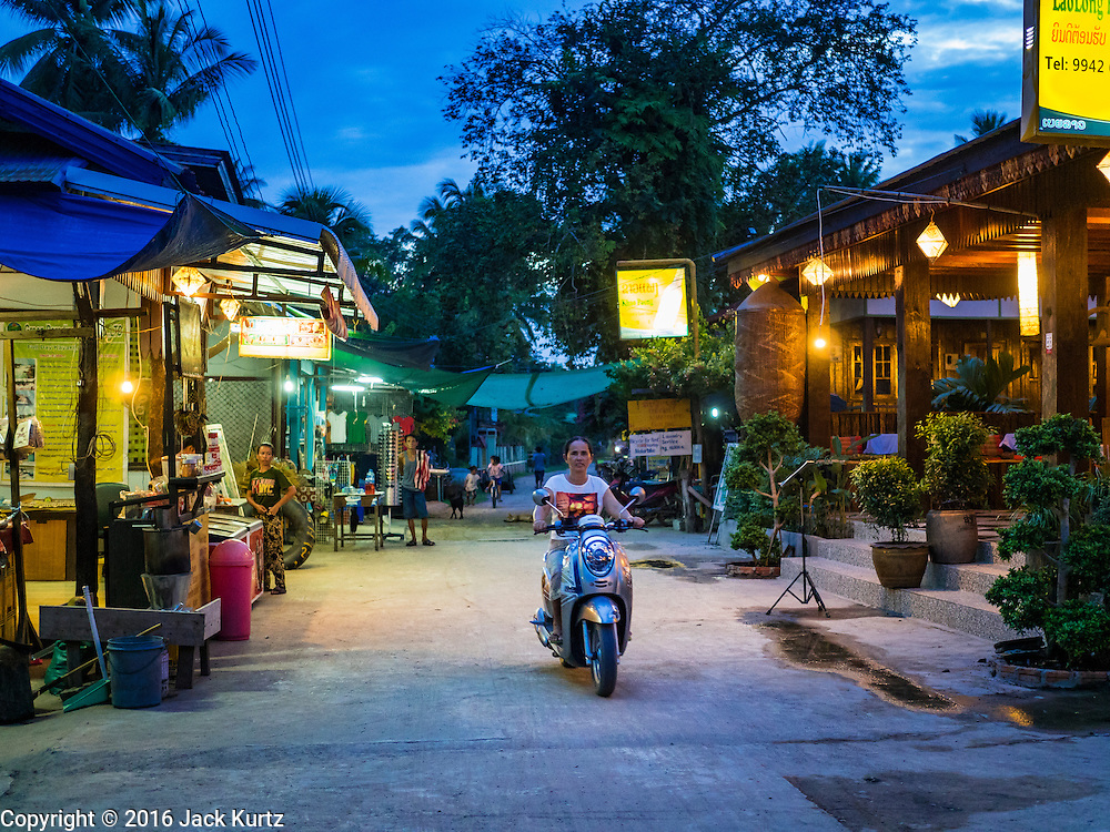 19 JUNE 2016 - DON KHONE, CHAMPASAK, LAOS: A woman rides her scooter on the main street in Don Khone village on Don Khone Island. Don Khone Island, one of the larger islands in the 4,000 Islands chain on the Mekong River in southern Laos. The island has become a backpacker hot spot, there are lots of guest houses and small restaurants on the north end of the island.      PHOTO BY JACK KURTZ