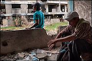 Un migrante guatemalteco (en primer plano, derecha) y un mexicano (al fondo) toman un descanso por la tarde en los restos de los condominios Monte Albán en Mexicali, Baja California.  Los edificios, derrumbados  tras el paso de terremotos y  deshabitados oficialmente desde el ocurrido en el 2010, son ahora hogar de varias decenas de personas, entre migrantes sin trabajo y 'tecolotes' o personas adictas.  (FOTO: Prometeo Lucero)