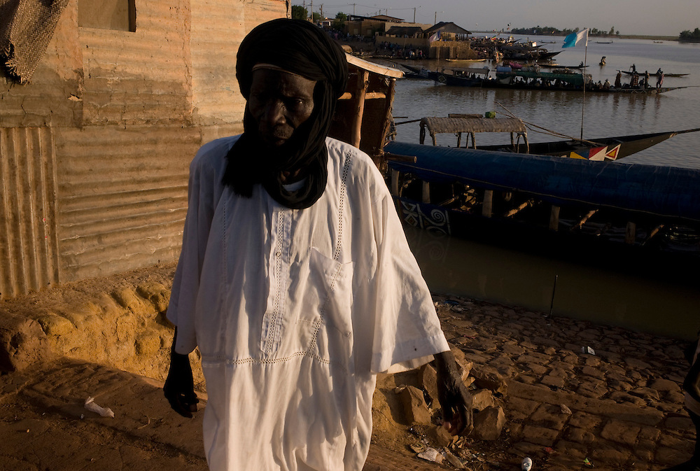 A man dressed with touareg clothes, unload a boat in Mopti's harbour. At the confluence of the Niger and the Bani rivers, between Timbuktu and Segou, Mopti is the second largest city in Mali, and the hub for commerce and tourism in this west-african landlocked country.