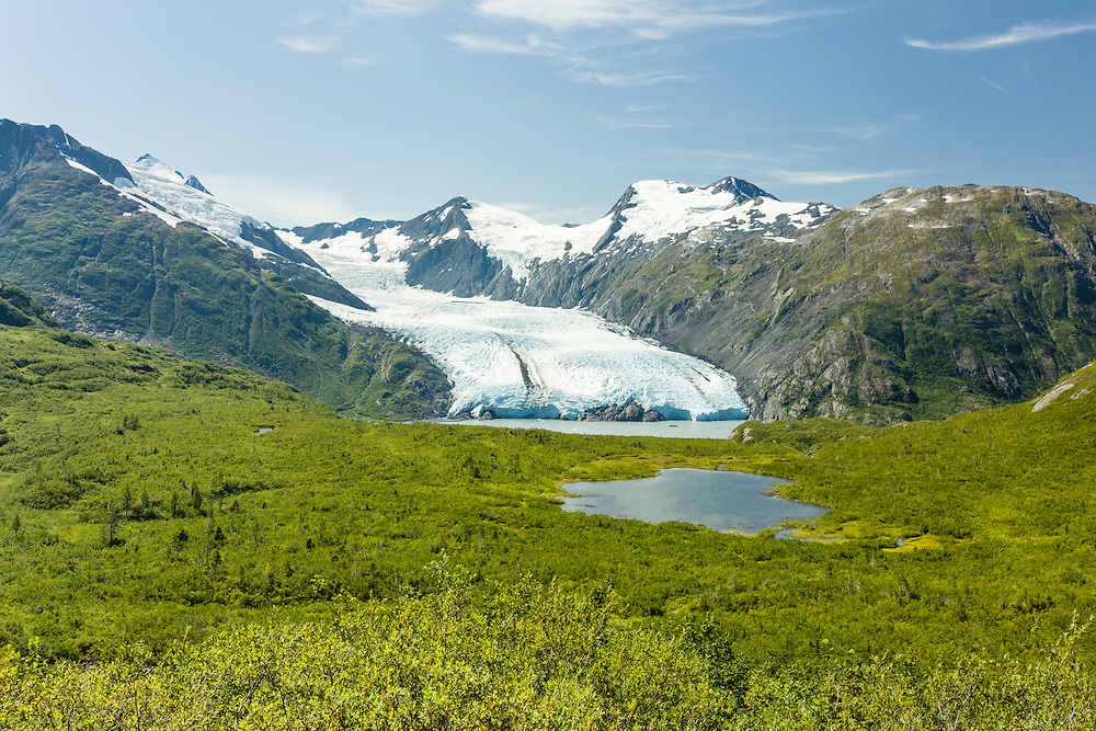 Scenic view of Portage Glacier and tour boat on Portage Lake with Divide Lake in foreground from Portage Pass in Chugach National Forest in Southcentral Alaska. Summer. Afternoon.