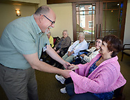 Chaplain Blaik Westhoff (cq) greets patient Carmen Reyes, 79, (right) during Spirit Alive, a religious service for people with dementia that incorporates Montessori principles Wednesday, June 28, 2017 at Meadow Glen Personal Care in Richlandtown, Pennsylvania. (WILLIAM THOMAS CAIN / For The Philadelphia Inquirer)