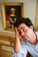 .winemaker Louis-Michel Liger-Belair in his Chateau in Vosne-Romanee, Burgundy..Behind are portraits of his ancestors, including the large painting of Comte Louis Liger-Belair, who was a general with Napoleon I...Photo by Owen Franken for the NY Times..May 27, 2008.