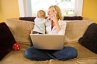 A mnid-30s Caucasian mother holds her curious son while talking on the phone in front of a laptop computer.