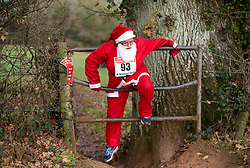 © Licensed to London News Pictures. 03/12/2017. Chew Magna, North Somerset, UK. Susan Cole gets over a stile on the 5k course. (Runners agreed to be photographed for press and publicity) Over 500 Santas of all ages and fitness levels take part in the very first Chew Valley Santa Scramble. This Winter community event began with the children's 1k Mini Santa Scramble starting off the morning's action, in the grounds of Chew Valley School. Then 325 children over 11years and adults ran, walked or skipped around a 5k route from Chew Valley School, taking in the beautiful countryside of Chew Stoke and Chew Magna. Everyone wears a Santa Suit, included in the entry fee. Both events were officially started by Bristol's inspiring adventurer, Jim Plunkett-Cole – also known as Jim 'Gump' who, having completed his Jim Gump Challenge of running across America, educating and inspiring children to get active along the way, is now doing the same amongst local schools in the area, to encourage children to enjoy an active and healthy lifestyle. The event was organised by Chew Valley School's BTEC students in Sports Management and the Chew Valley 10k team. All funds raised will be divided between Chew Valley School, who are fundraising to provide two undercover tennis courts and Mend The Gap (www.mendthegap.org.uk), a local charity based in Langford, which the school is linked to. Photo credit: Simon Chapman/LNP