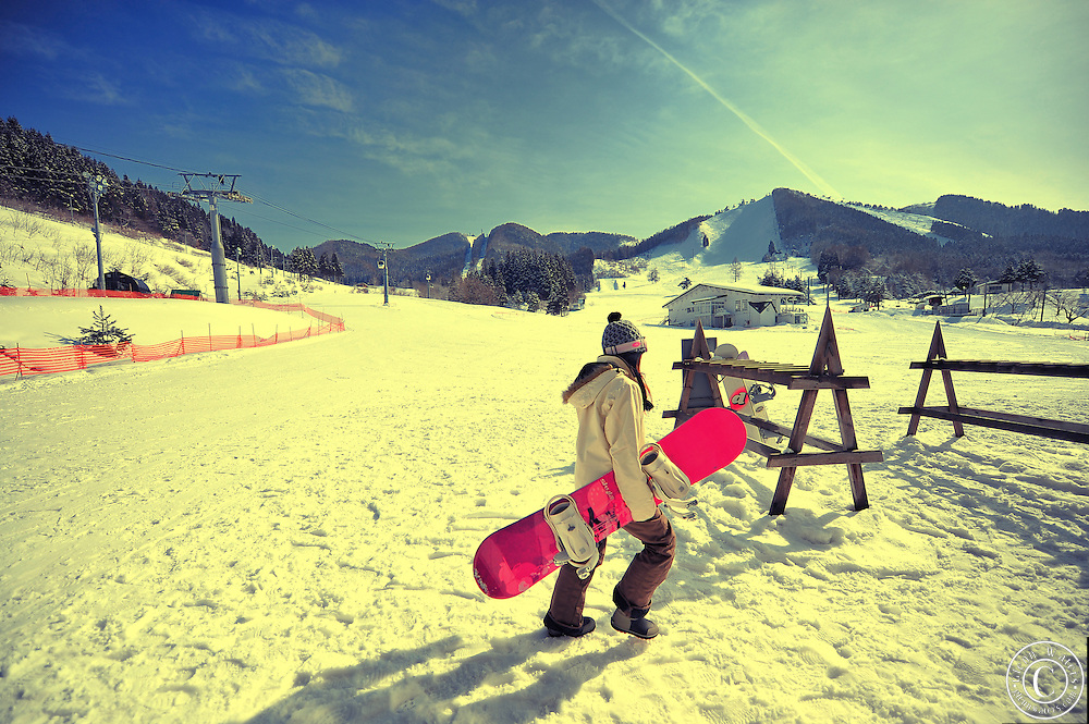 Wintersports at Owani ski field near Aomori in northern Japan.A young lady with a snowboard.