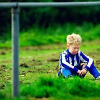 Nederland, Muiden, 07 september 2002.<br /> Amateurvoetbal, Pupillen F, 7-tal, 4e klasse.<br /> Muiden F2-Diemen F7    3-1<br /> Een speler van Diemen F7 is huilend buiten het veld gaan zitten en wil niet meer meespelen omdat hij in een duel onderuit gehaald is.<br /> Foto:Klaas Jan van der Weij