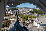 """Rooftop view of Himeji Castle, built 1609, Hyogo Prefecture, Japan. Himeji Castle is both a national treasure and a UNESCO World Heritage Site. Unlike many other Japanese castles, it was never destroyed by war, earthquake or fire and survives to this day as one of the country's twelve original castles. History: Starting as forts built in 1333 and 1346, Himeji Castle (aka White Heron Castle or White Egret Castle) was remodeled in 1561, remodeled in 1581, enlarged in 1609 to its present complex, extensively repaired in 1956, and renovated in 2009-15. Displayed inside are historic samurai armour and swords. From the upper floors, view fish-shaped roof ornaments that are believed to protect from fire. Across the moat, visit Koko-en, a pleasing reconstruction of former samurai quarters, nine Edo period homes, plus movie-set gardens. Himeji Castle starred in the 1967 James Bond movie """"You Only Live Twice""""; in Akira Kurosawa's 1980 film """"Kagemusha"""" and 1985 """"Ran""""; and in the 1980 television miniseries Shogun (portraying feudal Osaka castle). By train, Himeji is 3 hours round trip from Kyoto."""