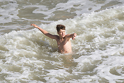 © Licensed to London News Pictures. 25/09/2016. Brighton, UK. Two youngster play in the sea in Brighton as strong waves and powerful gusts of wind are hitting the seaside resort. Photo credit: Hugo Michiels/LNP
