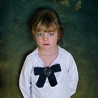 A young girl wearing a white cotton shirt and a black bow