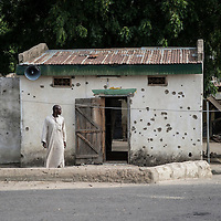 Gambarou, house riddled with bullets by Boko Haram. Due to violence by Boko Haram and the conflict between the group and Nigeria's military forces, thousands of people have been displaced in Borno state in Nigeria. In several locations in the region, people are living in enclaves and are prevented from leaving due to insecurity or restrictions. These enclaves are situated in camps or towns controlled by the military and are cut off from the outside world. People cannot farm, or keep up their livelihoods. They have either fled, or have been forcibly moved there and are now effectively stranded. The living conditions are deplorable, with people lacking basic food supplies, water and healthcare. Movement is restricted and people are totally reliant on outside aid, but insecurity prevents aid organisations from accessing these locations. MSF teams from Cameroon first managed to reach Ngala and Gambaru in Nigeria on September 19th. Ngala is a militarised camp hosting some 80.000 internally displaced people. It is situated some 7kms outside the town of Gambaru, where  its 123,000 residents also lack basic food supplies and have no access to healthcare after the town's only clinic was burnt down. Roads are too dangerous for people to go elsewhere for medical care. MSF teams found that 10 percent of children in Ngala and 15 percent of children in Gambaru were suffering from severe acute malnutrition and are in desperate need of assistance. MSF provided food and medical care and are scaling up assistance. Teams will distribute therapeutic food to severely malnourished children, vaccinate children against measles, conduct medical consultations, improve the water supply and distribute soap and non-food items. A general food distribution will be held in Ngala, ensuring the 80.000 residents of the camp receive food for two weeks.