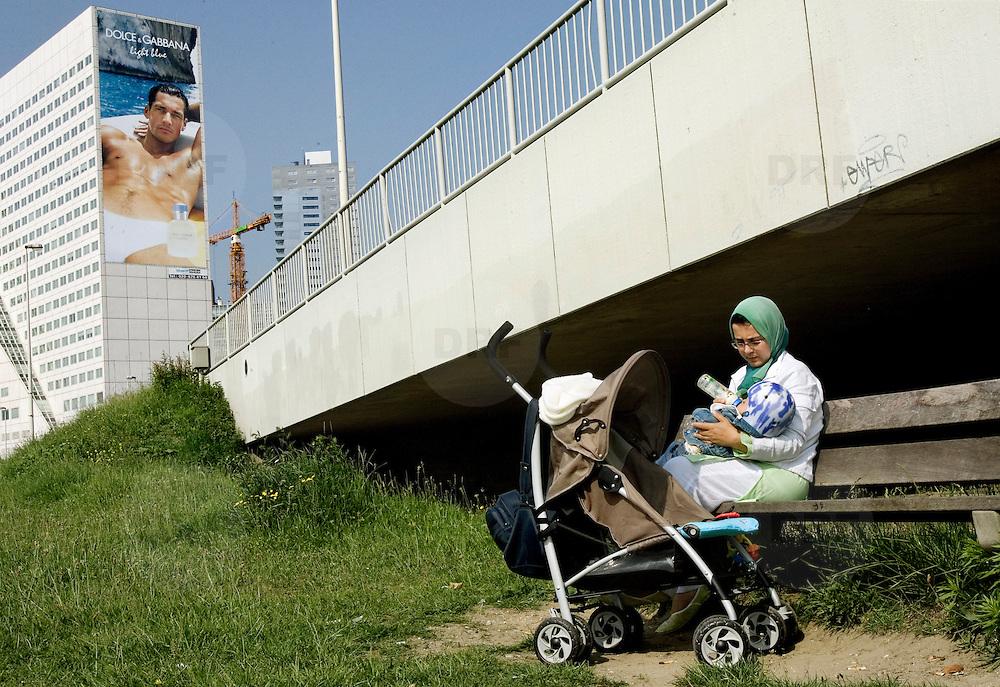 Nederland Rotterdam 7 juni 2007 20070607.Moslim vrouw voedt baby met de fles op een bankje aan de maasboulevard, op de achtergrond een reusachtig grote reclame met halfnaakte man van Dolce Gabbana op gebouw van Ernst & Young aan de Boompjes .Reclametechnieken: Bekend is de formule AIDA: attention, interest, desire, action: de aandacht opwekken, de interesse wekken, het verlangen opwekken, tot actie overhalen.Mental Preference: Techniek om mensen op een of meerdere van hun mentale denkstijlen aan te spreken: logisch; pragmatisch; emotioneel of creatief.Associatie: Reclamemakers proberen hun product te associ,ren met aangename of begeerlijke dingen om hun eigen product even begerig te maken. Hiervoor gebruiken ze modellen, landschappen en ander vergelijkbaar beeldmateriaal.Aspirationele leeftijd: Door de boodschap te richten op de aspirationele leeftijd van de doelgroep, wordt deze voor de daadwerkelijke doelgroep aantrekkelijker..Foto David Rozing