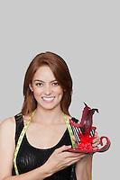 Portrait of female fashion designer holding stylish hat against colored background