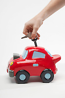 Hand Putting Car Keys in Car Shaped Piggy Bank