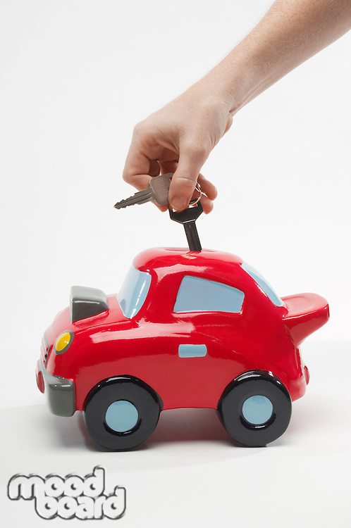 Hand Putting Car Keys in Car Shaped Piggy Bank