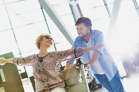 Man pushing baggage cart for check in while his wife is sitting in airport