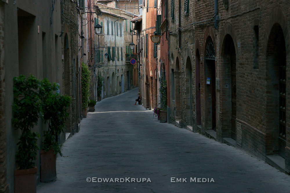A woman sits in a quiet street in the ancient village of Montalcino in Italy.