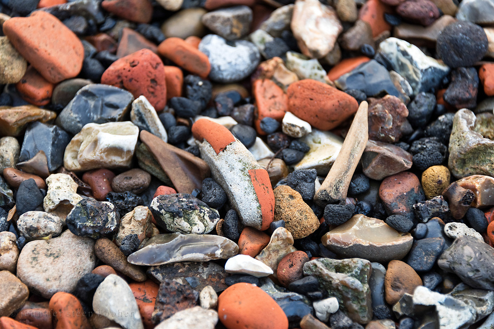 Brick rubble tumbled into a pebble shape, with old animal bones and fragments of flint and brick on the Thames shoreline, Greenwich, London.