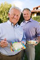Two senior man eating birthday cake