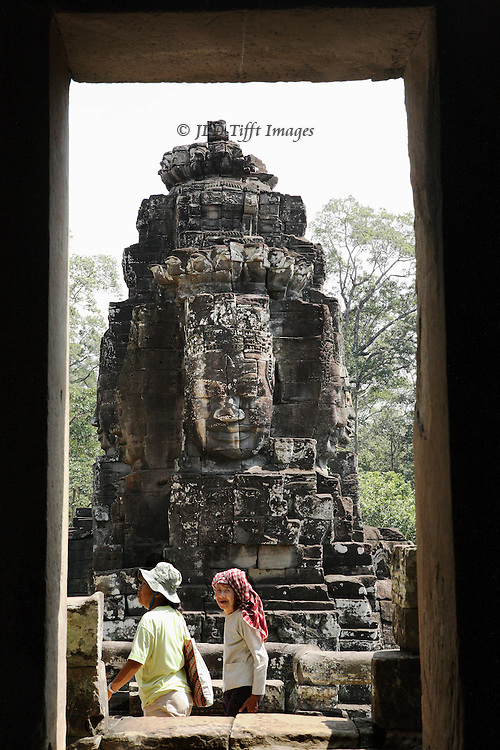 Angkor Thom, Bayon, four faced towers of the temple.  The giant heads, each facing a cardinal compass point as protection, may be portraits of Jayavarman VII, the king who built the temple XII century. A couple of tourists, one wearing a kaffiyeh, walk by the doorway in front of the sculptured tower.