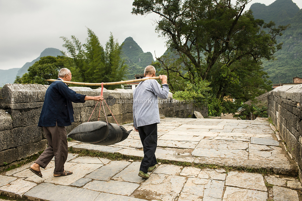 Two old men work together to carry a heavy black sack by suspending it from a bamboo rod between their shoulders.