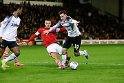 Conor Chaplin of Barnsley F.C. challenges Tom Lawrence of Derby County during the EFL Sky Bet Championship match between Barnsley and Derby County at Oakwell, Barnsley, England on 2 October 2019.