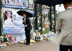 The Duke of Cambridge (foreground) and Prince Harry look at tributes to Diana, Princess of Wales attached to the Golden Gates of Kensington Palace, London, ahead of the 20th anniversary of their mother's death.