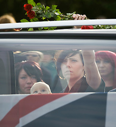 © licensed to London News Pictures. 08/09/2011. Brize Norton, UK. Joanne Weston wife of Sergeant Barry Weston holding her daughter Rose throwing roses on to the hearse carrying the coffin of Sergeant Barry Weston of 42 Commando Royal Marines as it passes through the town of Carterton, Oxfordshire today (08/09/2011). Today was the first time a repatriation had passed through RAF Brize Norton. Sgt Weston was killed on August 30 while leading a patrol near the village of Sukmanda in southern Nahr-e Saraj, Helmand province. Photo credit: Ben Cawthra/LNP