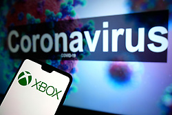 The XBOX logo seen displayed on a mobile phone with an illustrative model of the Coronavirus displayed on a monitor in the background. Photo credit should read: James Warwick/EMPICS Entertainment