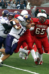 QB Russ Michna is grabbed by the Redbird defense