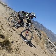 James Mulcahy from Queenstown in action during the New Zealand South Island Downhill Cup Mountain Bike series held on The Remarkables face with a stunning backdrop of the Wakatipu Basin. 150 riders took part in the two day event. Queenstown, Otago, New Zealand. 9th January 2012. Photo Tim Clayton