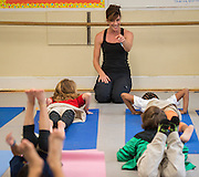 Yoga instructor Dee Boukouzis discusses teaching yoga with students during a session of Career Week at Poe Elementary School, December 5, 2013.