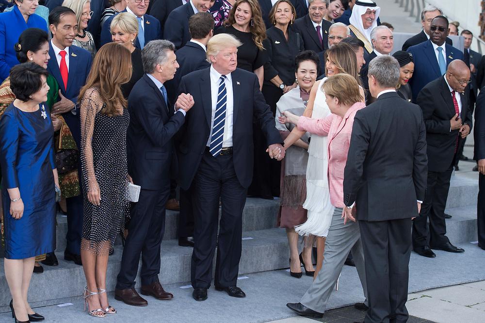 07 JUL 2017, HAMBURG/GERMANY:<br /> Kim Jeong-suk, Ehefrau von Moon Jae-in, Juliana Awada, Ehefrau von Mauricio Macri, Mauriocio Macri, Praesident von Argentinien, Donald Tump, Praesident Vereinigte Staaten von Amerika, USA, Peng Liyuan, Ehefrau von Xi Jinping, Melania Trump, Ehefrau von Donald Trump, Angela Merkel, CDU, Bundeskanzlerin, Joachim Sauer, Ehemann von Angela Merkel, (v.L.n.R.), Merkel weist Trump seine Platz in der zweiten Reihe zu, Familienfoto der G20 Teilnehmer und ihrer Partner vor der Elbphilharmonie<br /> IMAGE: 20170707-02-008<br /> KEYWORDS: G20 Summit, Deutschland, Elphi