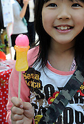 A young girl holds a lollypop candy during the Kanamara Festival in Kawasaki, Japan. Kanamara means metal phallus, so named after a story dating back hundreds of years in which a local blacksmith made an iron phallus to protect a girl who was thought to be curse. Today, the festival participants are largely prostitutes STDs.