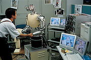Looking into the eyes of Jack the robot, Gordon Cheng tests its response to the touch of his hand. Researchers at the Electrotechnical Lab at Tsukuba, an hour away from Tokyo, Japan, are part of a project funded by the Japanese Science and Technology Agency to develop a humanoid robot as a research vehicle into complex human interactions. With the nation's population rapidly aging, the Japanese government is increasingly funding efforts to create robots that will help the elderly. Project leader Yasuo Kuniyoshi wants to create robots that are friendly and quite literally soft, the machinery will be sheathed in thick padding. In contrast to a more traditional approach, Kuniyoshi wants to program his robot to make it learn by analyzing and fully exploiting its natural constraints. From the book Robo sapiens: Evolution of a New Species, page 56-57.