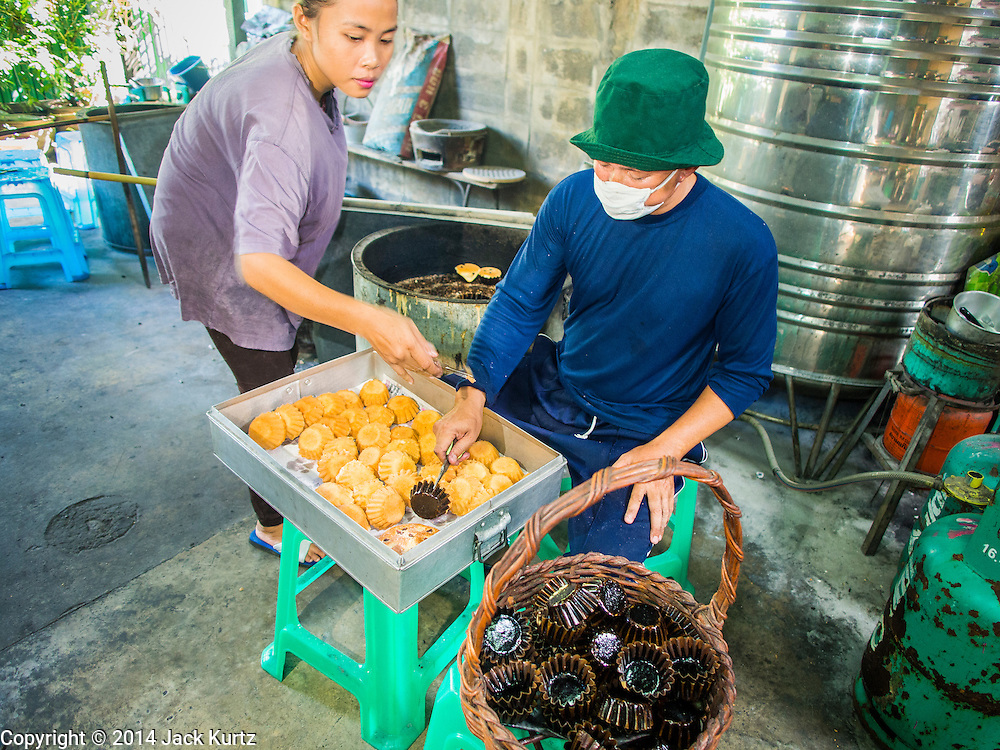 "28 OCTOBER 2014 - BANGKOK, THAILAND: Workers pull cakes out of the oven at the Pajonglak Maneeprasit Bakery in Bangkok. The cakes are called ""Kanom Farang Kudeejeen"" or ""Chinese Monk Candy."" The tradition of baking the cakes, about the size of a cupcake or muffin, started in Siam (now Thailand) in the 17th century AD when Portuguese Catholic priests accompanied Portuguese soldiers who assisted the Siamese in their wars with Burma. Several hundred Siamese (Thai) Buddhists converted to Catholicism and started baking the cakes. When the Siamese Empire in Ayutthaya was sacked by the Burmese the Portuguese and Thai Catholics fled to Thonburi, in what is now Bangkok. The Portuguese established a Catholic church near the new Siamese capital. Now just three families bake the cakes, using a recipe that is 400 years old and contains eggs, wheat flour, sugar, water and raisins. The same family has been baking the cakes at the Pajonglak Maneeprasit Bakery, near Santa Cruz Church, for more than 245 years. There are still a large number of Thai Catholics living in the neighborhood around the church.   PHOTO BY JACK KURTZ"