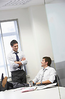 Two happy businessmen relaxing and talking in office