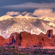 The La Sal Mountains, part of the Manti-La Sal National Forest and the southern Rocky Mountains, rise above the town of Moab, Utah, and Arches National Park, providing contrast to the hot red-rock landscape of Arches.