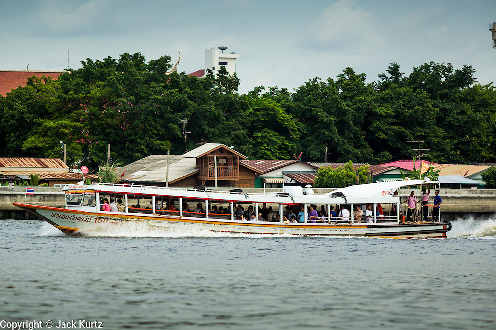 15 JULY 2014 - BANGKOK, THAILAND:    A Choa Phraya Express River Boat passes the pier for Wat Rachathiwat Ratchaworawihan on Samsen Soi 9. The temple has a large teak instruction hall, considered one of the finest teak buildings in Asia.   PHOTO BY JACK KURTZ