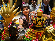 "11 APRIL 2017 - BANGKOK, THAILAND: Women bath a statue of the Buddha in scented water during the Songkran travel period at Hua Lamphong train station in Bangkok. Songkran is the traditional Thai Lunar New Year. It is celebrated, under different names, in Thailand, Myanmar, Laos, Cambodia and some parts of Vietnam and China. In most places the holiday is marked by water throwing and water fights and it is sometimes called the ""water festival."" This year's Songkran celebration in Thailand will be more subdued than usual because Thais are still mourning the October 2016 death of their revered Late King, Bhumibol Adulyadej. Songkran is officially a three day holiday, April 13-15, but is frequently celebrated for a full week. Thais start traveling back to their home provinces over the weekend; busses and trains going out of town have been packed.     PHOTO BY JACK KURTZ"