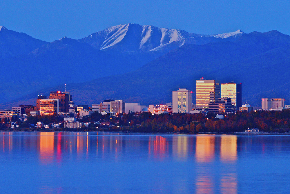 The Chugach mountain range stands above the downtown Anchorage skyline reflected in Cook Inlet.
