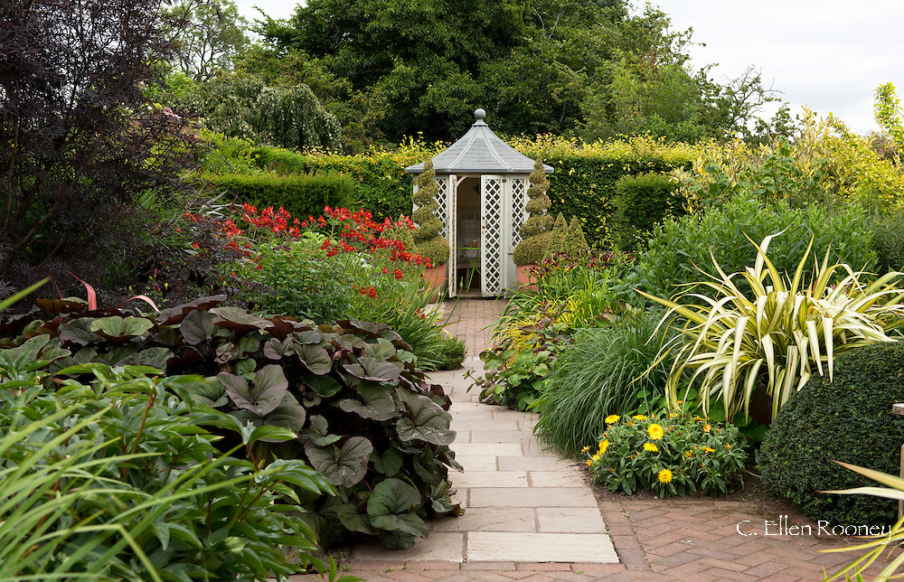 A summerhouse between double herbaceous borders along a brick and stone path at Wollerton Old Hall, Market Drayton, Shropshire, UK