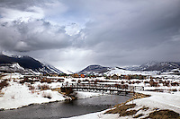 The unfrozen Slate River flows below this bridge near Crested Butte, Colorado as a late winter weather system rolls in.