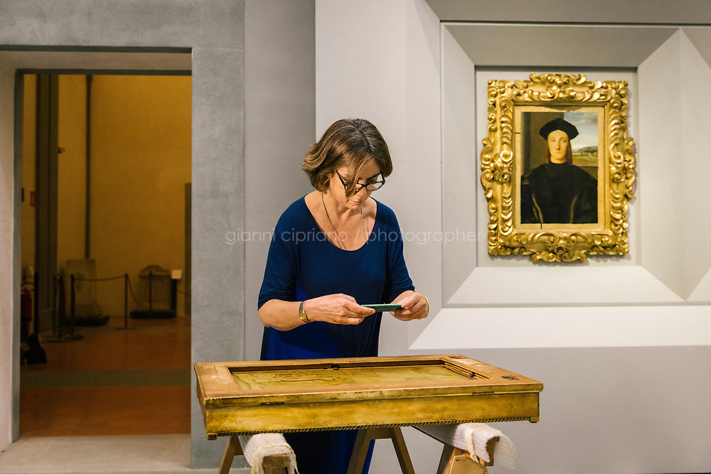 FLORENCE, ITALY - 3 JUNE 2018: Uffizi curator Francesca De Luca photographs a frame containging Raphael's portrait of Agnolo Tondi, here at its new location  in room 41at the Uffizi, in Florence, Italy, on June 3rd 2018.<br /> <br /> As of Monday June 4th 2018, Room 41 or the &ldquo;Raphael and Michelangelo room&rdquo; of the Uffizi is part of the rearrangement of the museum's collection that has<br /> been defining Uffizi Director Eike Schmidt&rsquo;s grander vision for the Florentine museum.<br /> Next month, the museum&rsquo;s Leonardo three paintings will be installed in a<br /> nearby room. Together, these artists capture &ldquo;a magic moment in the<br /> first decade of the 16th century when Florence was the cultural and<br /> artistic center of the world,&rdquo; Mr. Schmidt said. Room 41 hosts, among other paintings, the dual portraits of Agnolo Doni and his wife Maddalena Strozzi painted by Raphael round 1504-1505, and the &ldquo;Holy Family&rdquo;, that Michelangelo painted for the Doni couple a year later, known as the<br /> Doni Tondo.