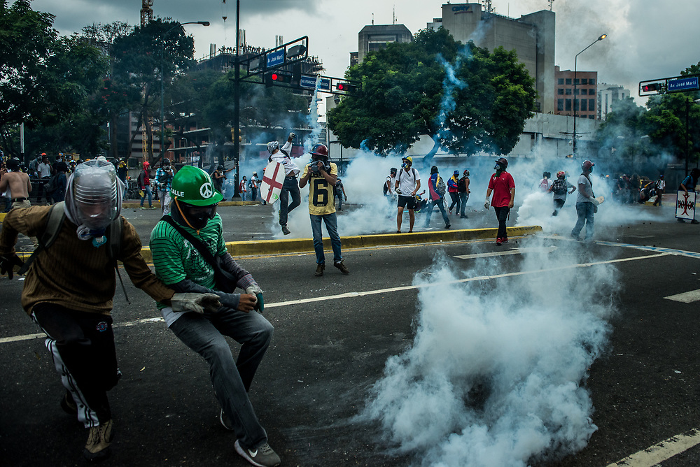 CARACAS, VENEZUELA - MAY 8, 2017:  Anti-government protesters throw rocks and molotov cocktails at members of the National Police, who responded by heavily tear gassing and firing rubber bullets and buckshot at them.  The streets of Caracas and other cities across Venezuela have been filled with tens of thousands of demonstrators for nearly 100 days of massive protests, held since April 1st. Protesters are enraged at the government for becoming an increasingly repressive, authoritarian regime that has delayed elections, used armed government loyalist to threaten dissidents, called for the Constitution to be re-written to favor them, jailed and tortured protesters and members of the political opposition, and whose corruption and failed economic policy has caused the current economic crisis that has led to widespread food and medicine shortages across the country.  Independent local media report nearly 100 people have been killed during protests and protest-related riots and looting.  The government currently only officially reports 75 deaths.  Over 2,000 people have been injured, and over 3,000 protesters have been detained by authorities.  PHOTO: Meridith Kohut