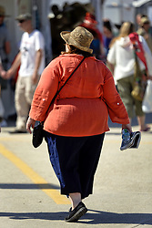 30 April 2015. New Orleans, Louisiana.<br /> The New Orleans Jazz and Heritage Festival. <br /> A large lady makes her way through the crowd. <br /> Photo; Charlie Varley/varleypix.com
