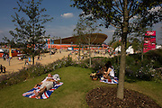 Brit spectators enjoy a hot summer on their union jack towels in the Olympic Park during the London 2012 Olympics, sitting on green grass located on a hilltop across from the iconic Velodrome venue. London's Olympic Park, at just under a square mile, is the largest new park in the city for more than 100 years. The planting of 4,000 trees, 300,000 wetland plants and more than 150,000 perennial plants plus  nectar-rich wildflower make for a colourful setting for the Games. This land was transformed to become a 2.5 Sq Km sporting complex, once industrial businesses and now the venue of eight venues including the main arena, Aquatics Centre and Velodrome plus the athletes' Olympic Village. After the Olympics, the park is to be known as Queen Elizabeth Olympic Park.