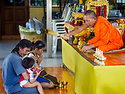 10 JULY 2018 - NAKHON PATHOM, THAILAND:  A Buddhist monk blesses a family at Phra Pathom Chedi in Nakhon Pathom. Nakhon Pathom is about 35 miles west of Bangkok. It is one of the oldest cities in Thailand, archeological evidence suggests there was a settlement on the site of present Nakhon Pathom in the 6th century CE, centuries before the Siamese empires existed. The city is widely considered the first Buddhist community in Thailand and the nearly 400 foot tall Phra Pathom Chedi is considered the first Buddhist temple in Thailand.    PHOTO BY JACK KURTZ