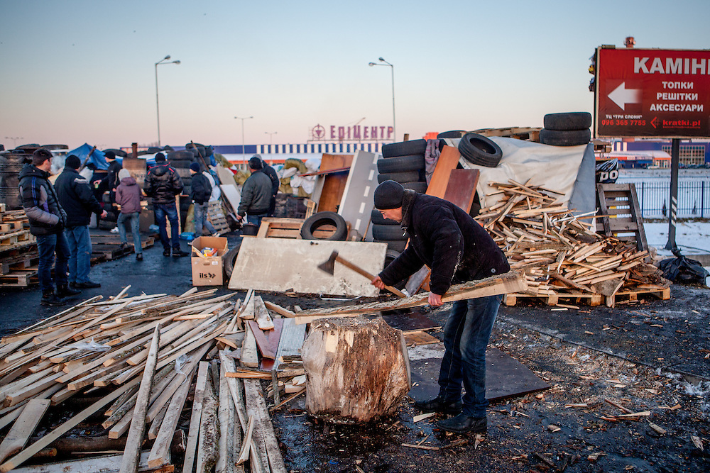 "Brother of Andrej is preparing fire wood with an axe at the barricades blockading a building supplies store named ""Epicenter"" in the city of Lviv, Ukraine."