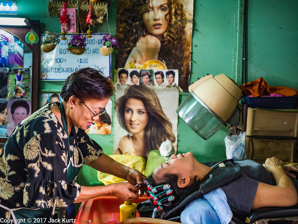 """06 FEBRUARY 2017 - BANGKOK, THAILAND: A customer (right) chats with her hairdresser in a shop in what used to be known as Kalabok Market under the Phra Khanong Bridge in the Phra Khanong district of Bangkok. Kalabok is the Thai word for hairdresser and the market was called Kalabok because there were many barbershops and hairdressers under the bridge. In 1985, the city changed the name of the market to """"Singha Market."""" There are still about 10 small men's barbershops, most with just one barber, and four women's salons, most with one hairdresser,  under the bridge.      PHOTO BY JACK KURTZ"""