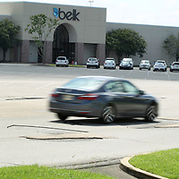 A car drive over the potholes on Mall Drive on Monday at The Mall at Barnes Crossing in Tupelo.